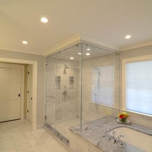Réalisation d'une salle de bain principale design de taille moyenne avec un placard à porte shaker, des portes de placard noires, une baignoire encastrée, une douche d'angle, un WC séparé, un carrelage de pierre, un mur gris, un sol en marbre, un lavabo encastré, un plan de toilette en marbre, un sol gris et une cabine de douche à porte battante.