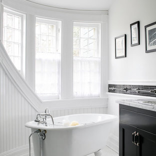 Claw-foot bathtub - victorian black and white tile claw-foot bathtub idea in Boston with shaker cabinets, black cabinets and white walls