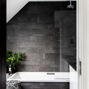 Mittelgroßes Modernes Duschbad mit flächenbündigen Schrankfronten, weißen Schränken, Einbaubadewanne, Duschbadewanne, grauen Fliesen, grauer Wandfarbe, Keramikboden, Unterbauwaschbecken, Granit-Waschbecken/Waschtisch, grauem Boden und schwarzer Waschtischplatte in London