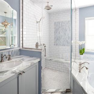 Идея дизайна: большая главная ванная комната в морском стиле с врезной раковиной, серыми фасадами, полновстраиваемой ванной, угловым душем, белой плиткой, плиткой кабанчик, синими стенами, мраморной столешницей, фасадами с утопленной филенкой, мраморным полом и сиденьем для душа
