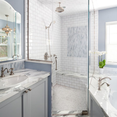 Example of a large beach style master white tile and subway tile marble floor bathroom design in Los Angeles with an undermount sink, gray cabinets, an undermount tub, blue walls, marble countertops and recessed-panel cabinets