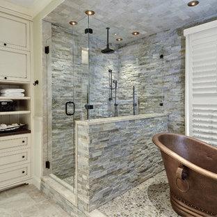 Modelo de cuarto de baño principal, clásico, grande, con armarios con paneles con relieve, puertas de armario blancas, bañera exenta, ducha empotrada, sanitario de dos piezas, baldosas y/o azulejos beige, baldosas y/o azulejos marrones, baldosas y/o azulejos grises, baldosas y/o azulejos de piedra, paredes beige, suelo de travertino, lavabo bajoencimera, encimera de granito, suelo beige y ducha con puerta con bisagras