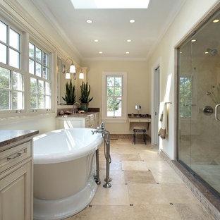 Idéer för att renovera ett stort vintage brun brunt en-suite badrum, med luckor med upphöjd panel, beige skåp, ett fristående badkar, en dusch i en alkov, beige kakel, cementkakel, gula väggar, klinkergolv i porslin, bänkskiva i kvarts, beiget golv och dusch med gångjärnsdörr