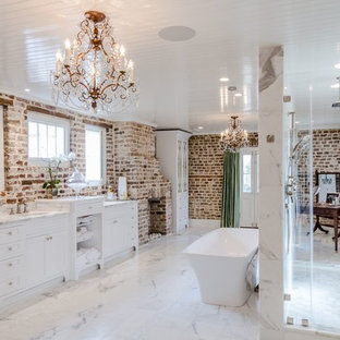 Inspiration for a large transitional master white tile marble floor and white floor bathroom remodel in Charleston with beaded inset cabinets, white cabinets, a one-piece toilet, multicolored walls, an undermount sink, marble countertops and a hinged shower door
