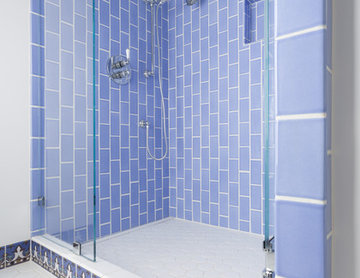 Shower in Sky Blue 3x6 subway tile with hexes on the floor.