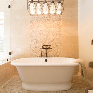 Idee per una stanza da bagno padronale mediterranea di medie dimensioni con ante in stile shaker, ante in legno scuro, vasca freestanding, WC monopezzo, piastrelle beige, piastrelle in travertino, pareti beige, pavimento in gres porcellanato, lavabo sottopiano, top in marmo, pavimento beige e porta doccia a battente