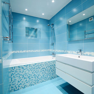 Modelo de cuarto de baño minimalista con lavabo suspendido, puertas de armario blancas, bañera empotrada, combinación de ducha y bañera, baldosas y/o azulejos azules y suelo azul