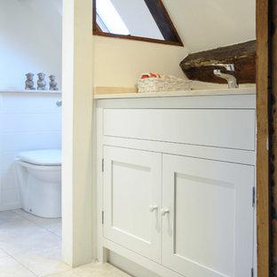 Immagine di una piccola stanza da bagno con doccia country con lavabo da incasso, ante in stile shaker, ante bianche, top in onice, piastrelle beige, piastrelle in ceramica, pareti bianche e WC monopezzo