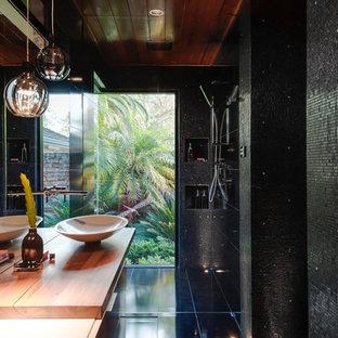 Idee per una piccola stanza da bagno padronale design con lavabo a bacinella, ante lisce, top in legno, doccia ad angolo, WC sospeso, piastrelle nere, piastrelle a mosaico e pavimento con piastrelle in ceramica