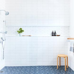 Idee per un'ampia stanza da bagno padronale minimalista con ante beige, piastrelle bianche, piastrelle in ceramica, pareti bianche, pavimento con piastrelle in ceramica, pavimento blu, doccia aperta e top bianco
