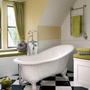 Kleines Klassisches Badezimmer mit Schrankfronten mit vertiefter Füllung, weißen Schränken, Löwenfuß-Badewanne, weißen Fliesen, Keramikfliesen, Porzellan-Bodenfliesen und gelber Wandfarbe in Surrey