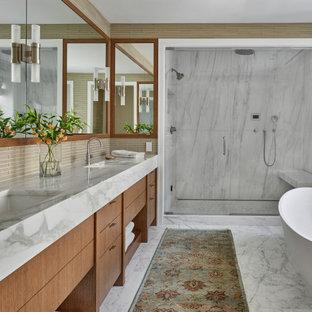 Пример оригинального дизайна: главная ванная комната среднего размера в стиле неоклассика (современная классика) с плоскими фасадами, фасадами цвета дерева среднего тона, отдельно стоящей ванной, угловым душем, бежевой плиткой, плиткой из листового стекла, бежевыми стенами, мраморным полом, врезной раковиной, мраморной столешницей, белым полом, душем с распашными дверями, белой столешницей, сиденьем для душа, тумбой под две раковины и встроенной тумбой