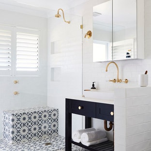 Inspiration for a 3/4 bathroom in Other with shaker cabinets, black cabinets, a corner shower, white tile, white walls, ceramic floors, a vessel sink and white benchtops.