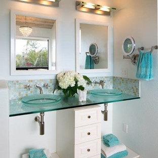 Modelo de cuarto de baño principal, costero, de tamaño medio, con armarios con paneles empotrados, puertas de armario blancas, bañera encastrada, ducha doble, bidé, baldosas y/o azulejos multicolor, baldosas y/o azulejos de vidrio, paredes azules, suelo de baldosas de cerámica, lavabo sobreencimera, encimera de vidrio, suelo beige y ducha con puerta con bisagras