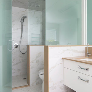 Inspiration for a large contemporary master white tile and marble tile marble floor and multicolored floor bathroom remodel in Calgary with flat-panel cabinets, white cabinets, an undermount sink, white walls, engineered quartz countertops, a hinged shower door and brown countertops