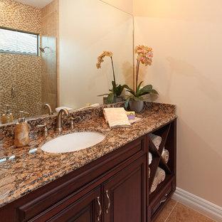 Ejemplo de cuarto de baño con ducha, tropical, de tamaño medio, con armarios con paneles con relieve, puertas de armario de madera oscura, paredes beige, suelo de piedra caliza, encimera de terrazo y suelo beige