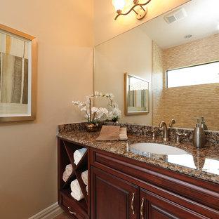 Immagine di una stanza da bagno con doccia tropicale di medie dimensioni con ante con bugna sagomata, ante in legno scuro, pareti beige, pavimento in pietra calcarea, top alla veneziana e pavimento beige