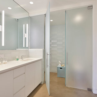 Design ideas for a large contemporary family bathroom in San Francisco with flat-panel cabinets, white cabinets, a built-in shower, white tiles, glass tiles, white walls, concrete flooring, a submerged sink, engineered stone worktops, a two-piece toilet and a hinged door.