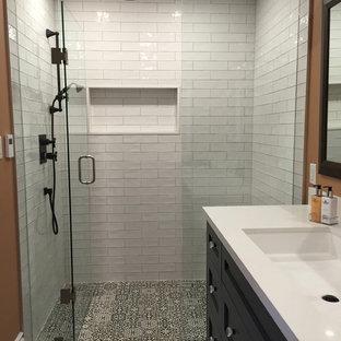 Ispirazione per una piccola stanza da bagno con doccia design con ante con riquadro incassato, ante nere, doccia alcova, pareti arancioni, pavimento con piastrelle in ceramica, lavabo sottopiano e top in superficie solida
