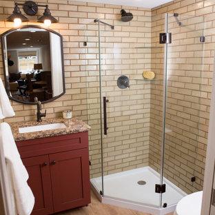Kleines Duschbad mit Schrankfronten im Shaker-Stil, roten Schränken, Eckdusche, Toilette mit Aufsatzspülkasten, beigefarbenen Fliesen, Keramikfliesen, beiger Wandfarbe, Vinylboden, Unterbauwaschbecken, Quarzwerkstein-Waschtisch, beigem Boden, Falttür-Duschabtrennung, beiger Waschtischplatte, Einzelwaschbecken und eingebautem Waschtisch in Sonstige