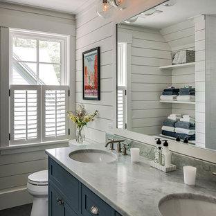 Diseño de cuarto de baño infantil, de estilo americano, con armarios estilo shaker, puertas de armario azules, baldosas y/o azulejos blancos, paredes blancas, suelo de baldosas de porcelana, lavabo bajoencimera, encimera de granito, suelo gris y encimeras grises