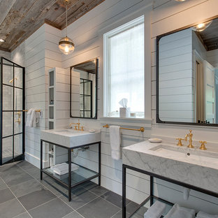 This is an example of a farmhouse ensuite bathroom in Other with grey tiles, white walls, a vessel sink, marble worktops and a hinged door.