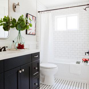 Diseño de cuarto de baño tradicional renovado con armarios estilo shaker, puertas de armario negras, bañera empotrada, combinación de ducha y bañera, baldosas y/o azulejos blancas y negros, baldosas y/o azulejos blancos, paredes blancas y lavabo bajoencimera