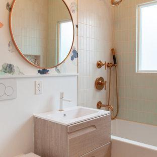 На фото: ванная комната в скандинавском стиле с плоскими фасадами, светлыми деревянными фасадами, ванной в нише, душем над ванной, инсталляцией, зеленой плиткой, разноцветными стенами, полом из терраццо, монолитной раковиной, разноцветным полом и белой столешницей с