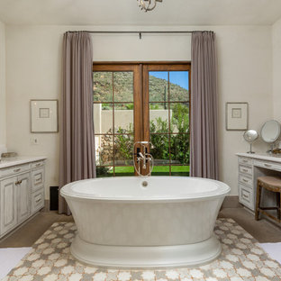 Tuscan gray floor freestanding bathtub photo in Phoenix with recessed-panel cabinets, gray cabinets, white walls, an undermount sink and white countertops