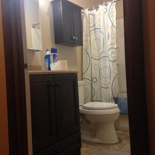 シカゴの小さいトラディショナルスタイルのおしゃれなマスターバスルーム (落し込みパネル扉のキャビネット、濃色木目調キャビネット、アルコーブ型浴槽、シャワー付き浴槽、分離型トイレ、ベージュの壁、クッションフロア、一体型シンク、オニキスの洗面台、ベージュの床、シャワーカーテン) の写真