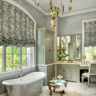 Elegant beige tile marble floor freestanding bathtub photo in St Louis with gray walls, green cabinets, raised-panel cabinets and an undermount sink