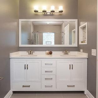 Ejemplo de cuarto de baño principal, minimalista, de tamaño medio, con puertas de armario blancas, bañera empotrada, combinación de ducha y bañera, sanitario de dos piezas, baldosas y/o azulejos grises, paredes grises, suelo de baldosas de cerámica, armarios con rebordes decorativos, lavabo bajoencimera y encimera de mármol