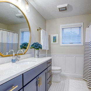 Inspiration for a large transitional 3/4 porcelain floor, white floor, single-sink and wainscoting bathroom remodel in Other with shaker cabinets, blue cabinets, a two-piece toilet, beige walls, an undermount sink, white countertops and a built-in vanity