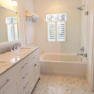 Idee per una piccola stanza da bagno tradizionale con lavabo sottopiano, ante lisce, ante bianche, top in marmo, vasca ad alcova, vasca/doccia, WC a due pezzi, piastrelle bianche, piastrelle in ceramica, pareti bianche e pavimento in marmo