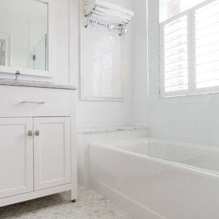 Klassisk inredning av ett litet badrum, med ett undermonterad handfat, släta luckor, vita skåp, marmorbänkskiva, ett badkar i en alkov, en dusch/badkar-kombination, en toalettstol med separat cisternkåpa, vit kakel, keramikplattor, vita väggar och marmorgolv