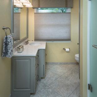 Diseño de cuarto de baño principal, clásico, de tamaño medio, con armarios con paneles con relieve, puertas de armario verdes, ducha empotrada, paredes amarillas, suelo de baldosas de porcelana, lavabo bajoencimera, encimera de acrílico, suelo gris y ducha con puerta con bisagras
