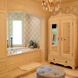 Photo of a large traditional master bathroom in New Orleans with an undermount sink, white cabinets and marble floors.