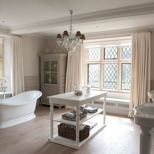 Inspiration for a farmhouse ensuite bathroom in Gloucestershire with a console sink, marble worktops, a freestanding bath, white walls and light hardwood flooring.