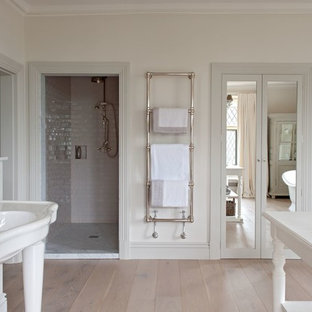 Photo of a rural ensuite bathroom in Gloucestershire with a pedestal sink, a freestanding bath, an alcove shower, white tiles, ceramic tiles, white walls and light hardwood flooring.