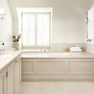 Foto på ett vintage beige en-suite badrum, med luckor med infälld panel, beige skåp, ett undermonterat badkar, vita väggar, ett undermonterad handfat och beiget golv