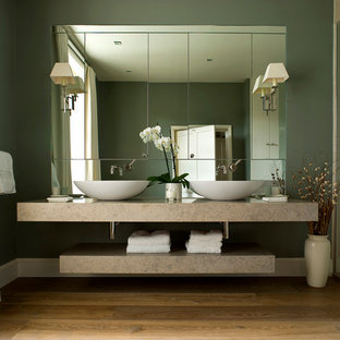 Contemporary master bathroom in London with green walls, medium hardwood floors and a vessel sink.