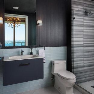 マイアミのコンテンポラリースタイルのおしゃれなバスルーム (浴槽なし) (フラットパネル扉のキャビネット、青いキャビネット、アルコーブ型シャワー、一体型トイレ、青いタイル、ガラスタイル、黒い壁、コンソール型シンク、グレーの床、クオーツストーンの洗面台、ベージュのカウンター) の写真