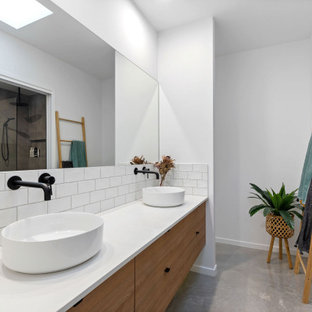 This is an example of a large contemporary 3/4 bathroom in Sunshine Coast with flat-panel cabinets, medium wood cabinets, white tile, subway tile, white walls, a vessel sink, grey floor, white benchtops, a double vanity and a floating vanity.