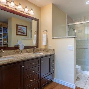 Foto di una stanza da bagno padronale chic di medie dimensioni con ante marroni, doccia ad angolo, WC a due pezzi, piastrelle beige, lastra di pietra, pareti gialle, pavimento in legno massello medio, lavabo sottopiano, top in granito, pavimento marrone, porta doccia scorrevole e top beige
