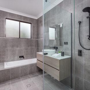 Inspiration för ett mellanstort funkis vit vitt badrum med dusch, med släta luckor, skåp i ljust trä, ett undermonterat badkar, grå kakel, ett fristående handfat och grått golv