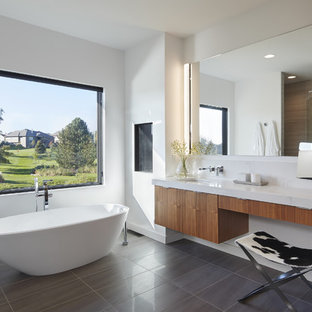 Photo of a modern ensuite bathroom in Minneapolis with flat-panel cabinets, medium wood cabinets, a freestanding bath, white walls, a submerged sink and grey floors.