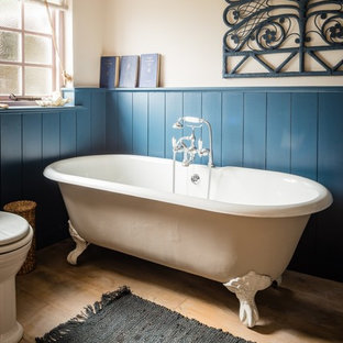 Photo of a medium sized mediterranean family bathroom in Cornwall with a claw-foot bath, a one-piece toilet, beige walls, light hardwood flooring and a console sink.