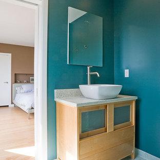 Idéer för ett modernt en-suite badrum, med granitbänkskiva, ett fristående handfat, luckor med glaspanel, skåp i ljust trä och blå väggar