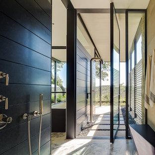 Ejemplo de cuarto de baño principal, actual, de tamaño medio, con bañera exenta, ducha abierta, baldosas y/o azulejos negros, losas de piedra, paredes negras, suelo de mármol y ducha abierta