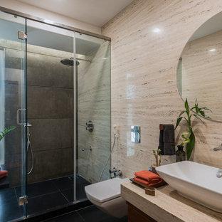 Diseño de cuarto de baño con ducha, actual, con ducha empotrada, sanitario de pared, baldosas y/o azulejos beige, losas de piedra, paredes beige, suelo de cemento, lavabo sobreencimera, suelo negro y ducha con puerta con bisagras